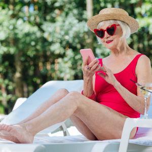 Äldre dam i baddräkt och solglasögon sitter på solstol och tittar leende på telefon