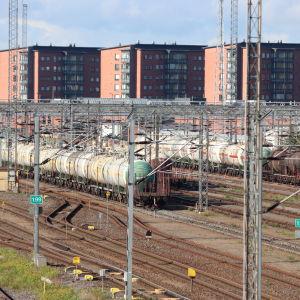 Godståg vid bangården i Åbo med höghus i bakgrunden.
