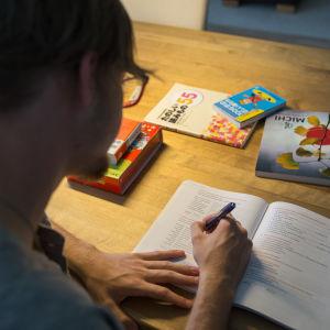 Ung man sitter vid skrivbord och gör skoluppgifter.