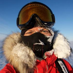 En kvinna iklädd en tjock vinterjacka med pälskantad huva, en balaklava som täcker allt utom ögonen och stora glasögon som hon för tillfället dragit upp på huvudet. Hon befinner sig på Grönland. Huvan är täckt av snö.