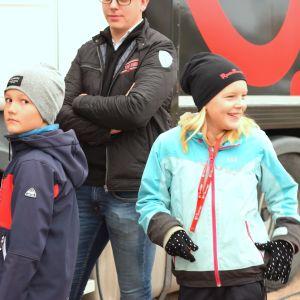 En pojke och en flicka stiger på en lastbil. Båda vänder sig om och blickar bakåt, flickan ler.