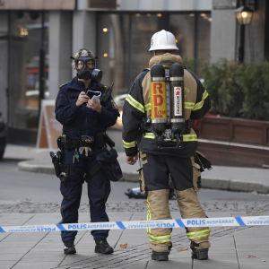 Polis med gasmask och brandman står innanför det avgränsade området i Östermalm där ett företag tagit emot en försändelse innehållande pulver.