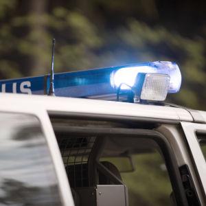 Polisbil med blåljusen på.