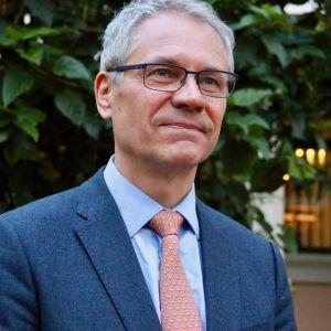 En gråhårig man i glasögon och blå kostym.