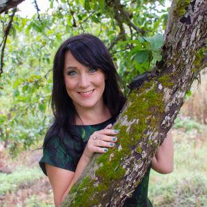Tuhkimotarinoiden ohjaaja Mape Morottaja hymyilee ja nojaa puuhun.