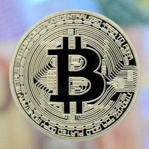 I förgrunden ett mynt med tecknet för bitcoin. i bakgrunden utsuddade eurosedlar.
