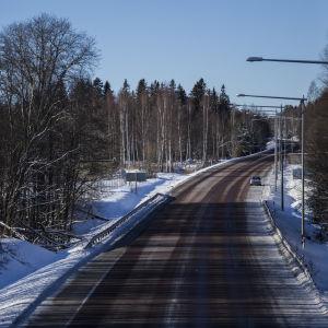 En bild på en väg, på bilden finns lyktstolpar och snö.