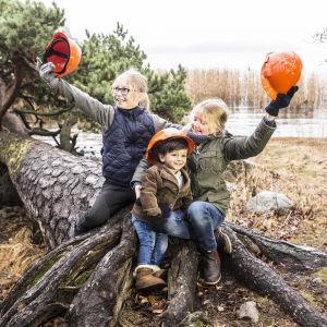 Barn sitter på fallet träd vid strand.