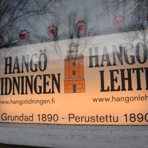 Ett skyltfönster som tillhör Hangötidningen. Där finns tydliga skyltar som visar att tidningsredaktionen finns inne i just det stenhuset.