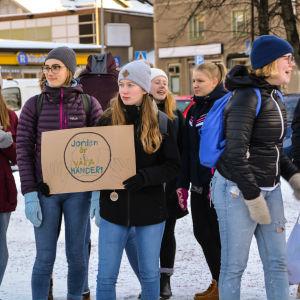 """Ungdomar protesterar mot klimatförändringen. I förgrunden synns två unga kvinnor varav den ena håller upp en skylt på vilken det står """"Jorden är i våra händer!""""."""