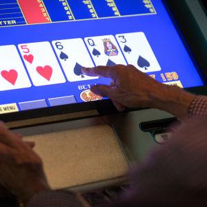 Lähikuva miehen käsistä pelaamassa rahapeliä Casino Helsingissä.