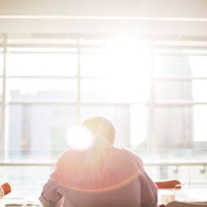 Man sitter ensam på jobb vid ett bord.