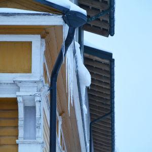 Ett tak som det hänger en stor istapp från.