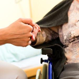 en vårdare håller en klient i handen.