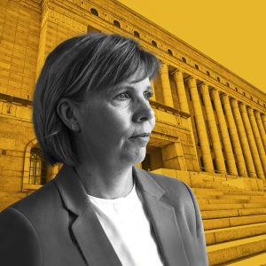 Anna-Maja Henriksson med riksdagshuset i bakgrunden. Bakgrunden har ett gult filter.