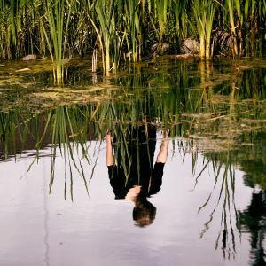 Bilden av en person reflekteras i vattnet.