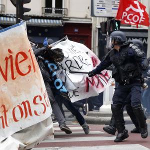 Poliisi otta yhteen mielenosoittajien kanssa Pariisissa, ranskankielisiä banderolleja