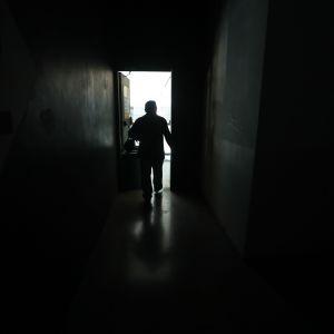En man går i en mörk korridor i ett Caracas som är mörkt på grund av strömavbrott.