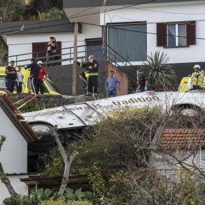 En bild på en vit buss som vält ner för ett stup och landat bland hus.