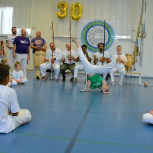 En pojke som utför capoeira. Runt honom sitter människor i en ring.