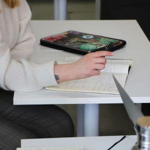 Studerande skriver anteckningar i ett häfte.