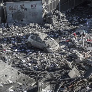 En bil mitt bland bråtet efter en sönderbombad byggnad i Gaza City på söndag morgon.