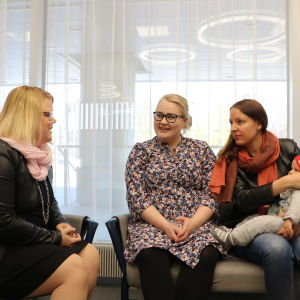 Tre kvinnor sitter inomhus på en soffa och talar. En kvinna har ett litet barn i famnen.