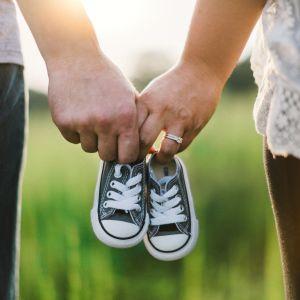 Miehen ja naisen kädet pitelevät lasten tennareita.