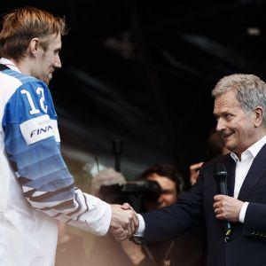 Republikens president Sauli Niinistö gratulerar guldkapten Marko Anttila.
