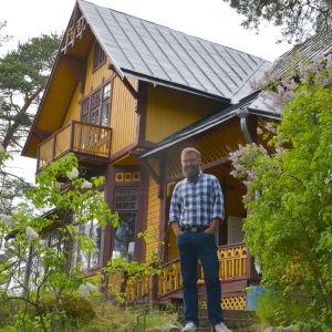 Berndt Arell vid några syrenbuskar framför det gula trähuset.