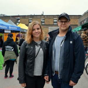 En man och en kvinna står på ett torg omringad av människor.