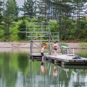Människor tar sig ner i vattnet från en brygga