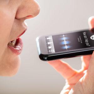 En kvinna pratar in i en telefonmikrofon.