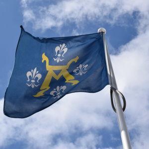 Åbo stads vapen på en blå flagga mot en blå himmel med lite moln.
