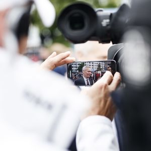 I bilden hålls en telefon, på telefonens skärm syns Antti Rinne som står en bit bort.