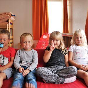 Barnen Kevin, Noel, Saga och Veronica sitter i en röd soffa, tittar in i kameran och ler.