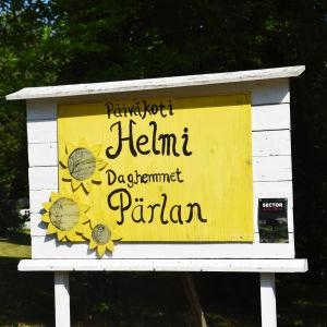 En gul skylt där det står päiväkoti Helmi, daghemmet Oärlan.