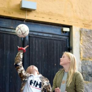 Två flickor kastar upp en fotboll.