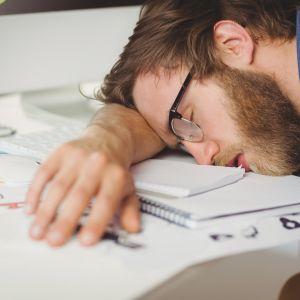 Man sover lutad mot sitt arbetsbord