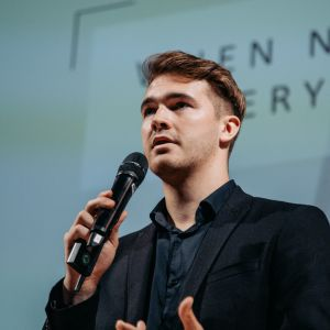 Close up photo of man talking with a microphone in his hands.