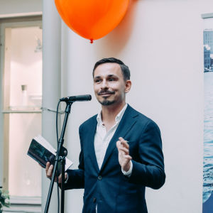 Man holding a book - talking in front a microphone, behind a white wall