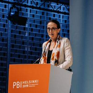 A woman speaking behind an orange PBI Helsinki 2019 podium in front of a blue wall.