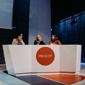 Three people engaged in a panel debate behind a white podium where the text PBI Helsinki 2019 is present.
