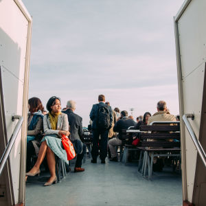 People sitting on the outside deck on a ferry.