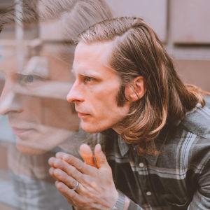 Mies puolipitkissä hiuksissa ja harmaassa flanellipaidassa katsoo mietteliäästi sivulle, hänen kätensä ovat yhteen painettuna hänen edessään. Miehen kasvot heijastuvat kuvan suurennettuina ja haaleampana hänen kasvojensa edessä.