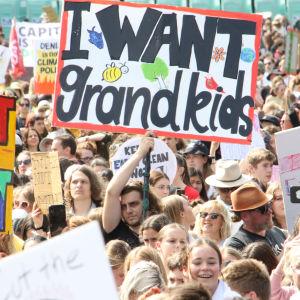 """En klimataktivist håller upp ett plakat med texten """"I wan't grandkids""""."""