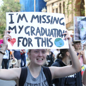 """En klimataktivist håller upp ett plakat med texten """"Im missing my graduation for this""""."""