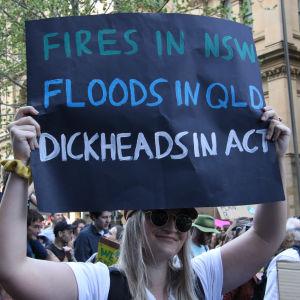 """En klimataktivist håller upp ett plakat med texten """"Fires i NSW, floods in QLD, dickheads in act""""."""