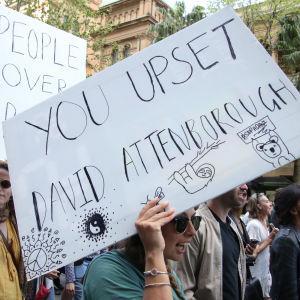 """En klimataktivist håller upp ett plakat med texten """"You upset David Attenborough""""."""