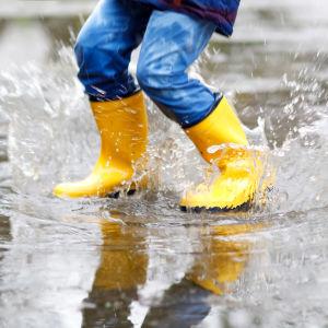 Barn i gummistövlar hoppar i vattenpöl
